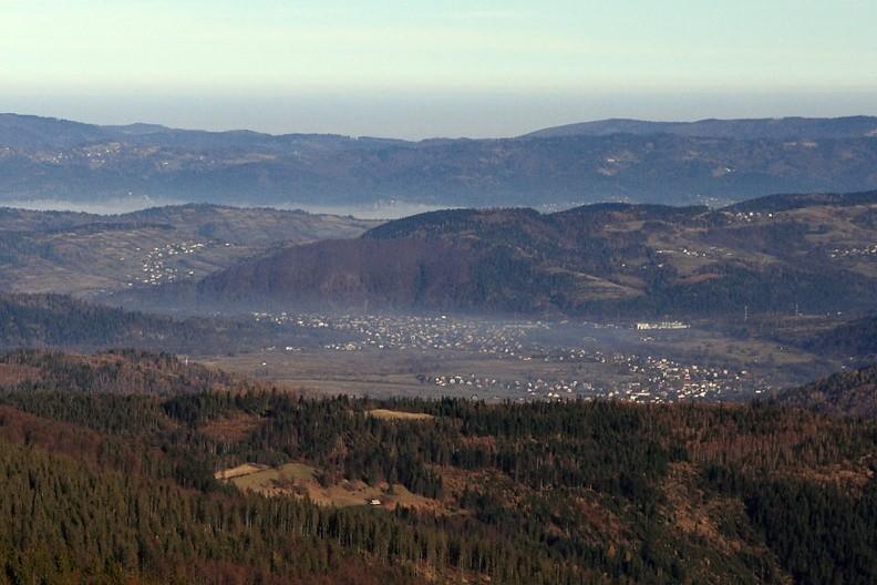 """23-IMG 1493 -- W oddali, za wschodnim ramieniem Łabysówki: Jeleśnia u podnóża Janikowej Grapy, która przechodzi – ku prawej stronie – w Madejów Groń i Garlejów Groń. Widoczną z lewej strony, rozpiętą na łagodnych zboczach Biedaszkowskiego Gronia literę """"S"""" tworzą zabudowania Mutnego. Jeszcze dalej, za wypełnionym mgłą obniżeniem doliny Łękawki wybrzusza się Beskid Mały: domki przy lewej krawędzi zdjęcia to Łysina na Ścieszków Groniu, zaś na ostatnim planie, po prawej stronie kadru wystaje Potrójna"""
