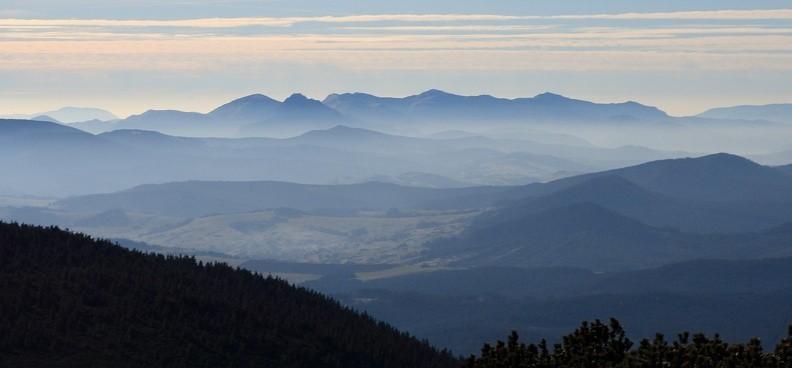 41-IMG 1576 -- Na południowym zachodzie widać krywańską część Małej Fatry. Pierwsza wybitniejsza góra od lewej to Stoh, drugi jest (wyrastający trochę bliżej) skalisty Veľký Rozsutec, potem w perspektywicznym skrócie widać grzbiet od Poludňovego grúňa do Chleba. Szeroka, płaskawa piramida to Veľký Kriváň, który obniża się do Pekelníka; drugą z piramid stanowi Malý Kriváň. Ciąg szczytów w tym planie zamyka Stratenec. Kolejny plan to znajdująca się już po drugiej stronie Wagu Luczańska Mała Fatra