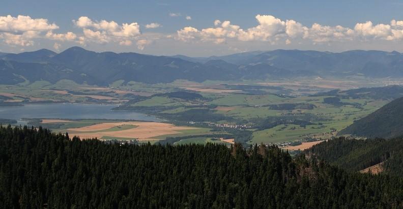 05-IMG 6518 -- Nieco dalej: połać Kotliny Liptowskiej ze zbiornikiem wodnym Liptovská Mara. Po lewej stronie wznoszą się Niżnie Tatry – zalesione grzbiety opadają od kopulastego Salatína. Białe budynki przy prawej krawędzi kadru to skrawek Ružomberoka. Miasto leży u stóp Wielkiej Fatry, którą od Niżnich Tatr oddziela dolina (niewidocznej stąd) Revúcy
