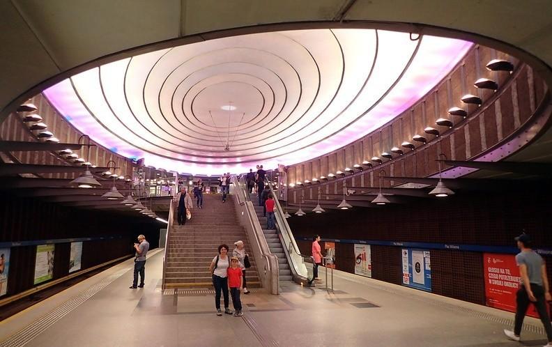 33-P7170097 -- Wróciliśmy pod ziemię. Ze śródmiejskiej stacji Ratusz Arsenał przejechaliśmy na Żoliborz. Stacja Plac Wilsona – naprawdę ładna. Spływające z elipsoidalnej kopuły światło zmienia barwę: teraz stacja jest fioletowa, lecz, zależnie od pory dnia, bywa czerwona, niebieska, żółta albo zielona. Poza tym zainstalowane nad naszymi głowami kręgi mają za zadanie tłumić hałas emitowany przez hamujące i ruszające składy metra