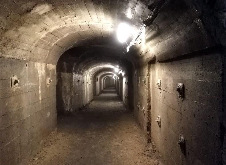 """06-IMG 150949 -- Oto najdłuższy z korytarzy, we wschodniej części podziemi. Znajdujące się na jego północnym krańcu (obecnie zamknięte) wyjście oddzielone jest od reszty obiektu betonową """"śluzą przeciwwybuchową"""". Obecność śluzy oraz specyficzny układ podziemi (odpowiednio ukierunkowujący energię ewentualnej wewnętrznej eksplozji) mogą skłaniać do wniosku, że pierwotnie planowano tu urządzić składowisko materiałów wybuchowych. W południowej części tego samego korytarza oglądamy z bliska sugestywne pęknięcie w ścianach i spągu – wynik działalności tektonicznej związanej z przebiegającym tędy (z północnego zachodu na południowy wschód) uskokiem będzińskim [Fot. z telefonu]"""