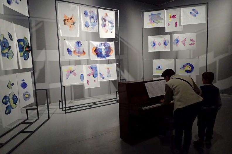 """44-P9140093 -- Sala Muzyczna. Na stelażach wisi """"partytura, oparta na cyklu obrazów <i>500 Azaleas</i> namalowanych przez Alexa Cecchettiego. [...] Partytura utworu jest gotowa, więc każdy z odwiedzających może go wykonać na pianinie, by posłuchać, jak brzmią kolorowe rysunki artysty przetransponowane na zapis nutowy"""""""